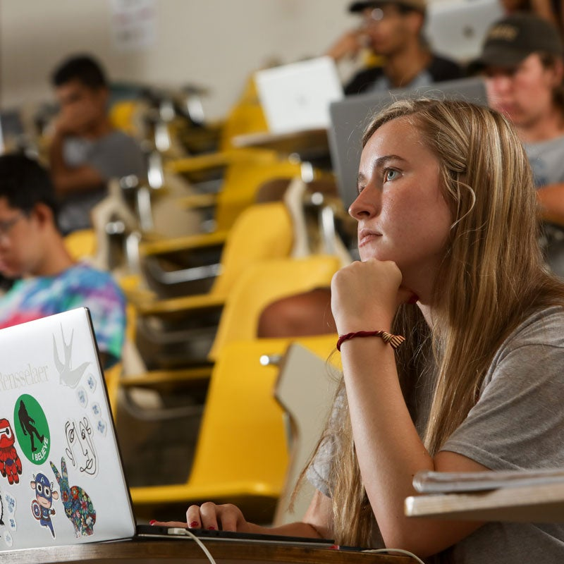 Female student with a laptop listening to a lecture