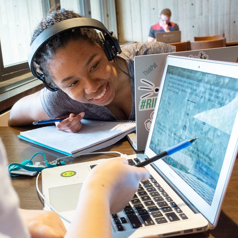 Smiling student being shown content on a laptop